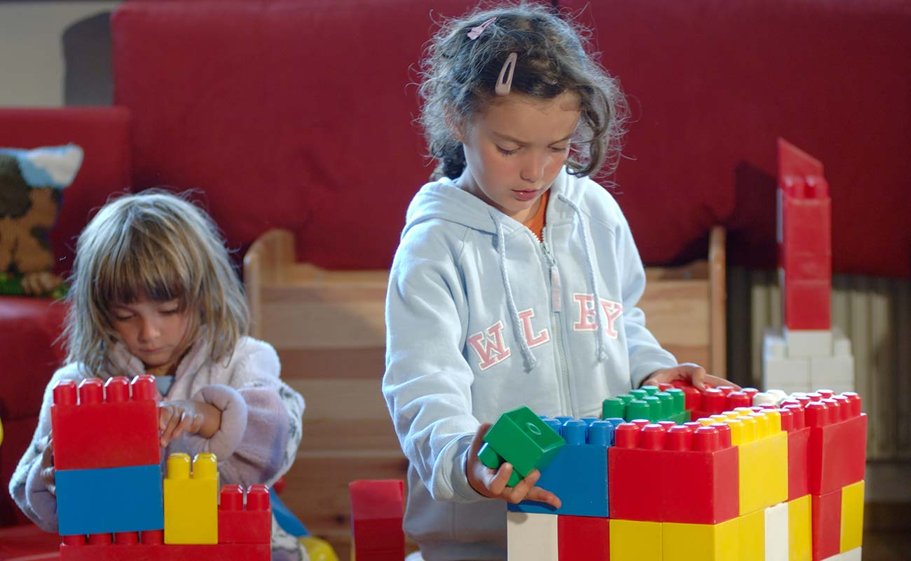 Two girls play in the playroom with large blocks of lego