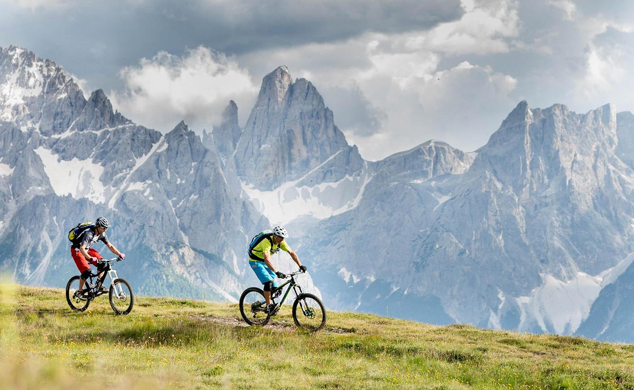 Two cyclists on a plateau and mountains of rock in the background